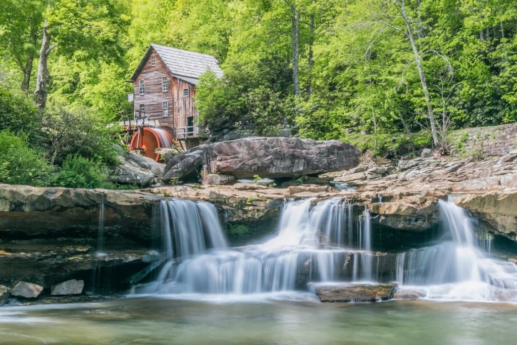 brown waterfalls near house and forest trees during daytime